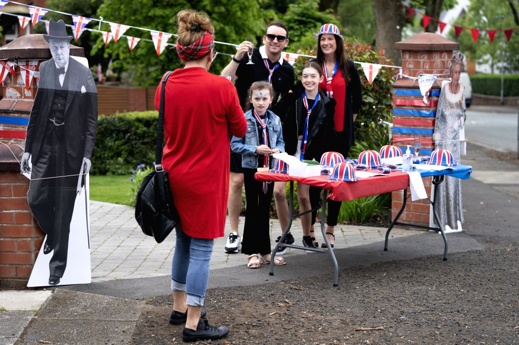 MANCHESTER (BRITAIN), May 8, 2020 A family poses for pictures at a street party to commemorate the 75th anniversary of of the end of World War II in Europe in Manchester, Britain, on May ...
