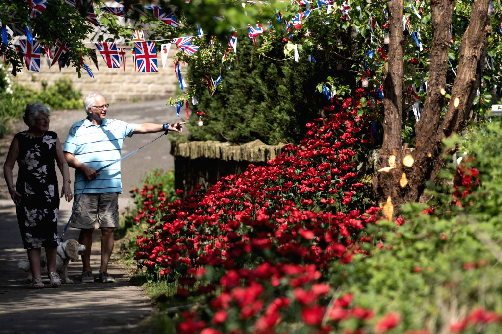 MANCHESTER (BRITAIN), May 8, 2020 People take a look at a floral tribute to the lives lost during the world wars in Manchester, Britain, on May 8, 2020. Britain held events on Friday ...