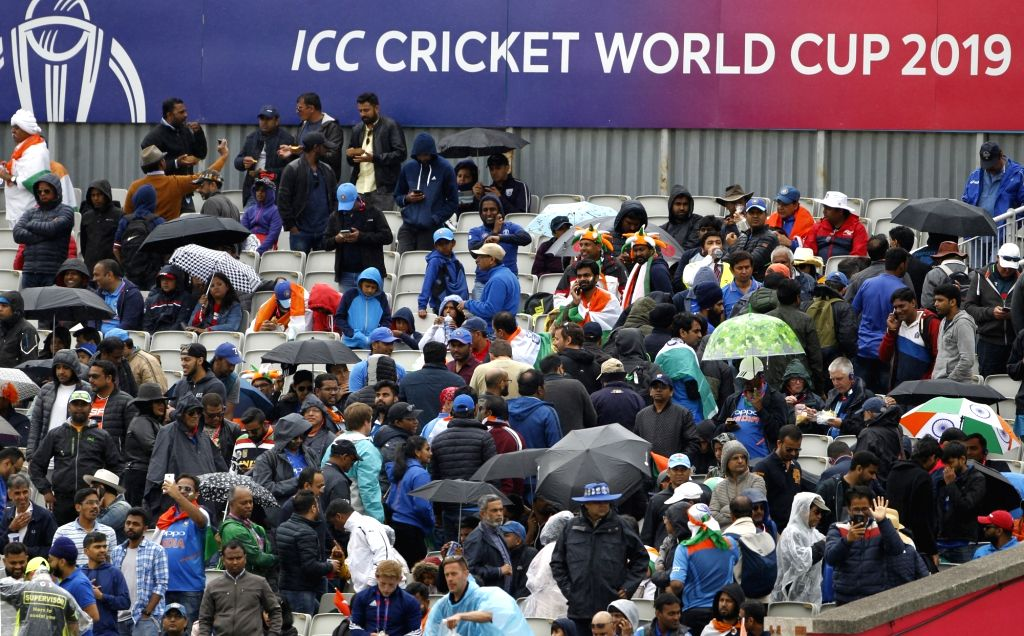 Manchester: Fans shield themselves with umbrellas after rains interrupt the 1st Semi-final match of 2019 World Cup between India and New Zealand at Old Trafford in Manchester, England on July 9, 2019. (Photo: Surjeet Kumar/IANS) - Surjeet Kumar