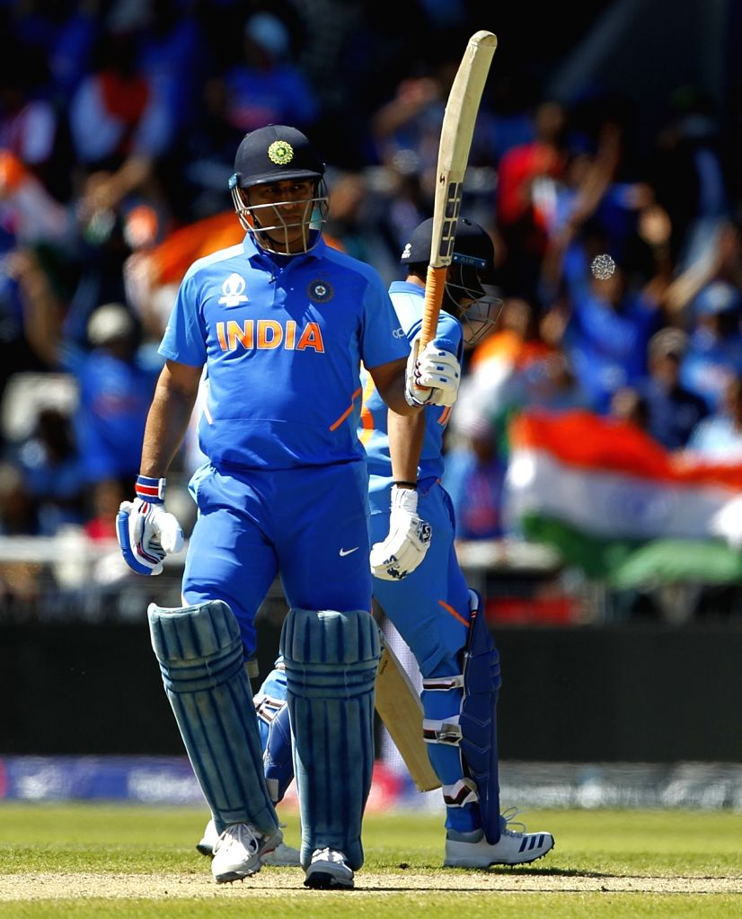 Manchester: India's MS Dhoni celebrates his half century during World Cup 2019 match between India and West Indies at Old Trafford in Manchester, England on June 27, 2019. (Photo: Surjeet Yadav/IANS) - MS Dhoni and Surjeet Yadav