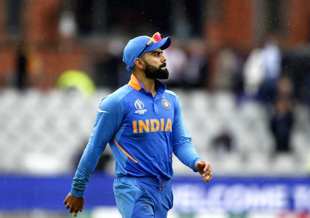 Manchester: Indian skipper Virat Kohli leaves the field after rains interrupt the 1st Semi-final match of 2019 World Cup between India and New Zealand at Old Trafford in Manchester, England on July 9, 2019. (Photo: Surjeet Kumar/IANS) - Virat Kohli and Surjeet Kumar