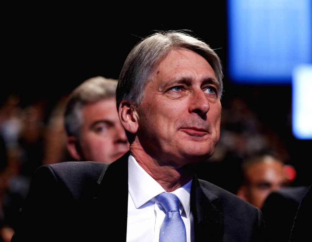 MANCHESTER, Oct. 4, 2017 - British Chancellor of the Exchequer Philip Hammond listens after handing a cough sweet to British Prime Minister Theresa May during her keynote speech to delegates and ... - Theresa May