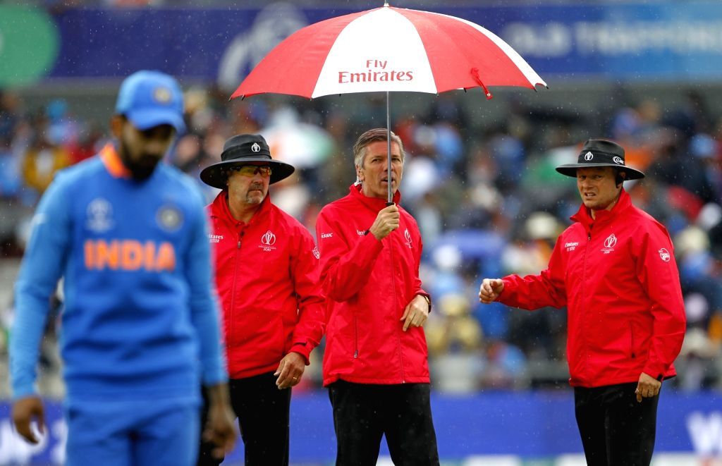 Manchester: Reserve Umpire Nigel Llong shields himself with an umbrella after rains interrupt the 1st Semi-final match of 2019 World Cup between India and New Zealand at Old Trafford in Manchester, England on July 9, 2019. (Photo: Surjeet Kumar/IANS) - Surjeet Kumar