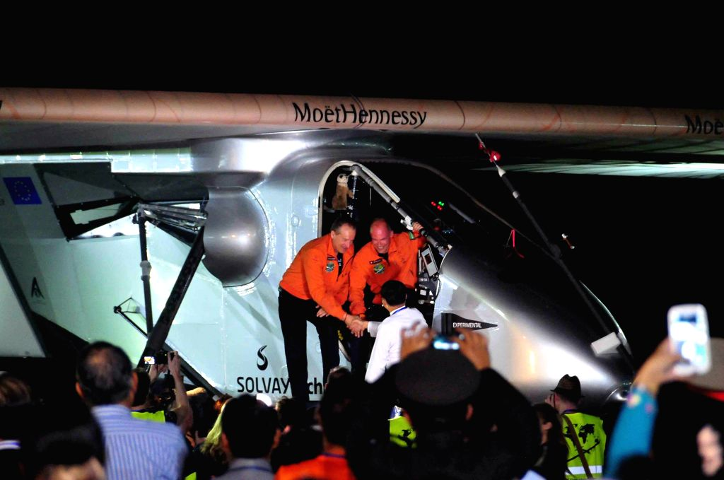 Swiss fighter pilot Bertrand Piccard (R Rear) greets officials after landing at Mandalay International Airport in Mandalay, Myanmar, March 19, 2015. Solar Impulse ...