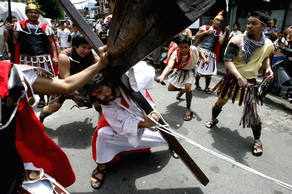 An actor playing the role of Jesus Christ is whipped by men dressed as centurions during a Passion Play on a street in Mandaluyong City, the Philippines, .