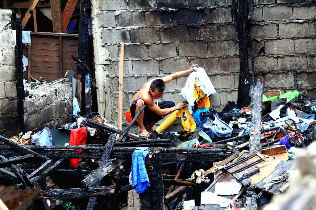A resident looks for reusable materials from the burnt home after a fire hit a residential area in Mandaluyong City, the Philippines, on July 3, 2014. The ..