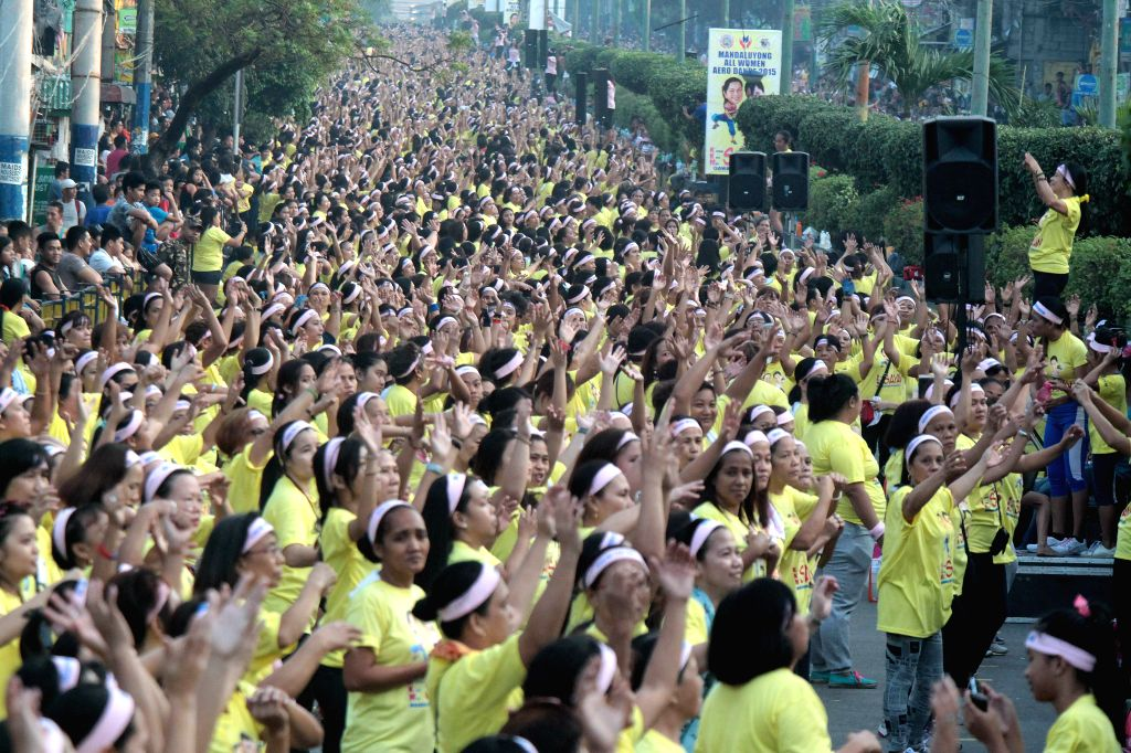"""Women exercise during the """"All-Women Aerodance"""" in Mandaluyong City, the Philippines, March 15, 2015. More than 26,000 women participated in the ..."""