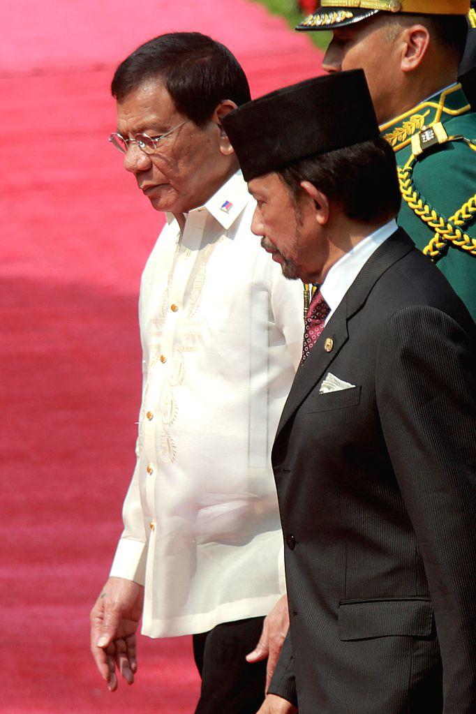 MANILA, April 27, 2017 - Philippine President Rodrigo Duterte (L) walks with Brunei Sultan Hassanal Bolkiah (R) in front of honor guard inside the Malacanan Presidential Palace in Manila, the ...