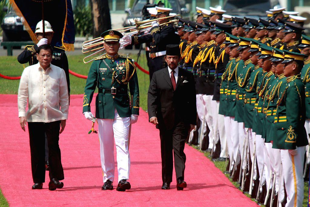 MANILA, April 27, 2017 - Philippine President Rodrigo Duterte (1st L) walks with Brunei Sultan Hassanal Bolkiah (3rd L) in front of honor guard inside the Malacanan Presidential Palace in Manila, the ...