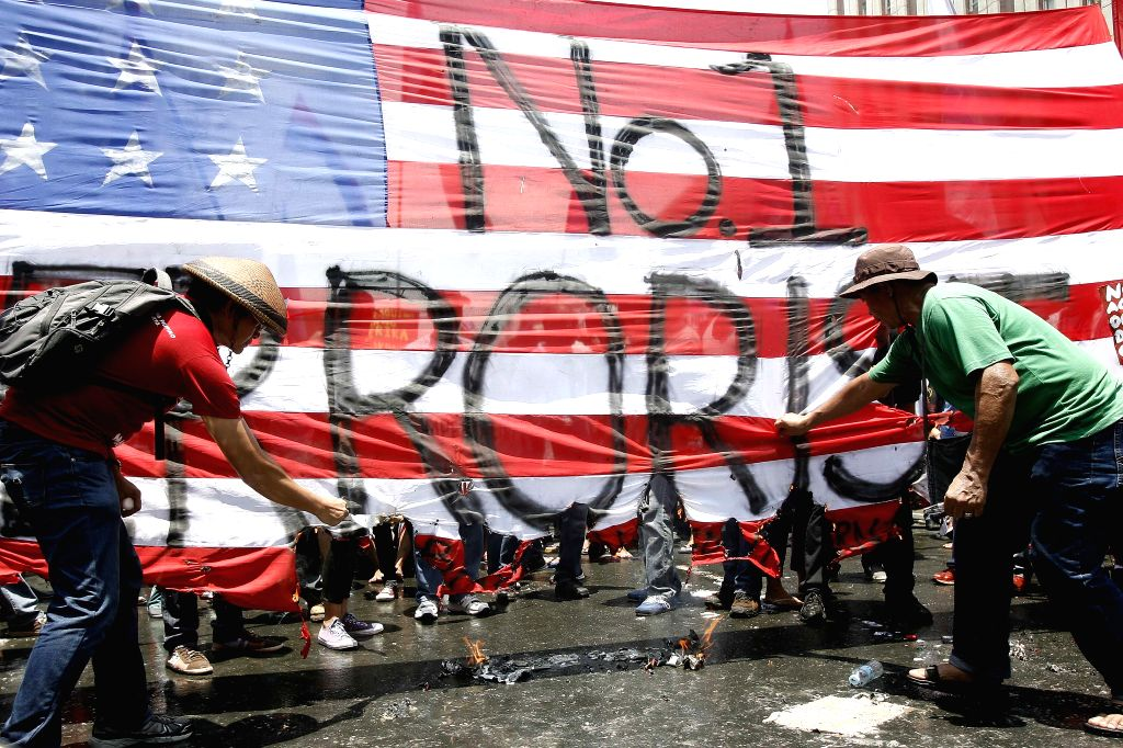Activists try to burn a mock U.S. flag during a protest rally near the U.S. Embassy in Manila, the Philippines, April 29, 2014. U.S. President Barack Obama on ...