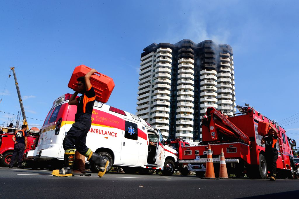 MANILA, April 29, 2019 - Firefighters carry equipment as they try to put out the fire engulfing the residential building named Pacific Coast Plaza in the Manila suburban city of Paranaque, the ...