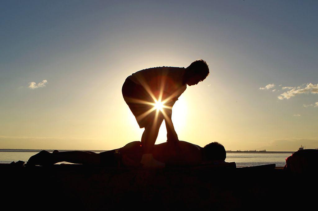 MANILA BAY, Jan. 8, 2019 - A man massages a tourist during sunset at Manila Bay in Manila, the Philippines, Jan. 8, 2019. Philippine President Rodrigo Duterte is trying to get around 876 million U.S. ...