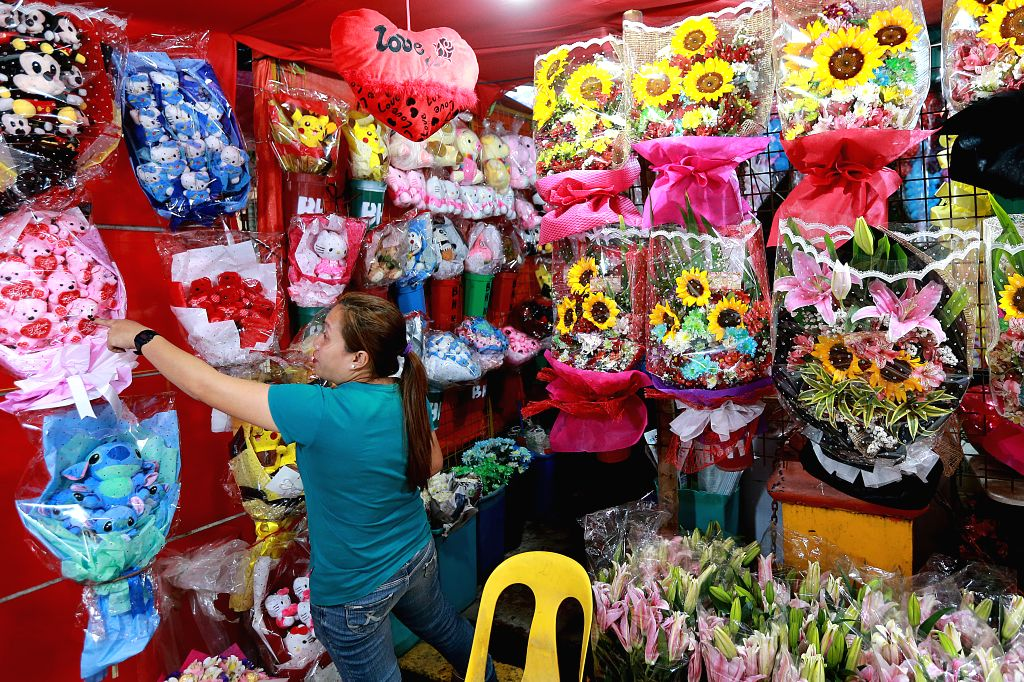 MANILA, Feb. 12, 2019 - A vendor arranges flowers for the upcoming Valentine's Day at a street of flower shops in Manila, the Philippines, Feb. 12, 2019.
