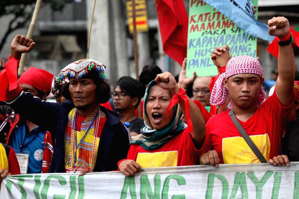 Indigenous people attend a rally against the militarization in their communities near the Malacanan Palace in Manila, the Philippines, Nov. 24, 2014. The protestors called for the end of ...