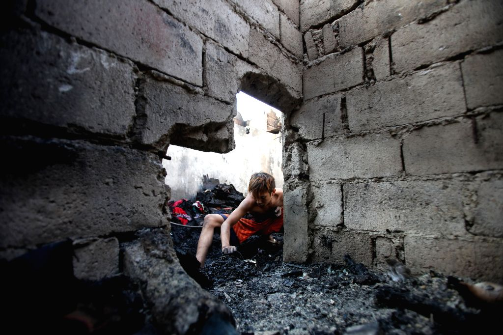 A resident looks for reusable materials after a fire hit a slum area in Manila, the Philippines, Jan. 13, 2015. More than 100 houses were razed in the fire, leaving .