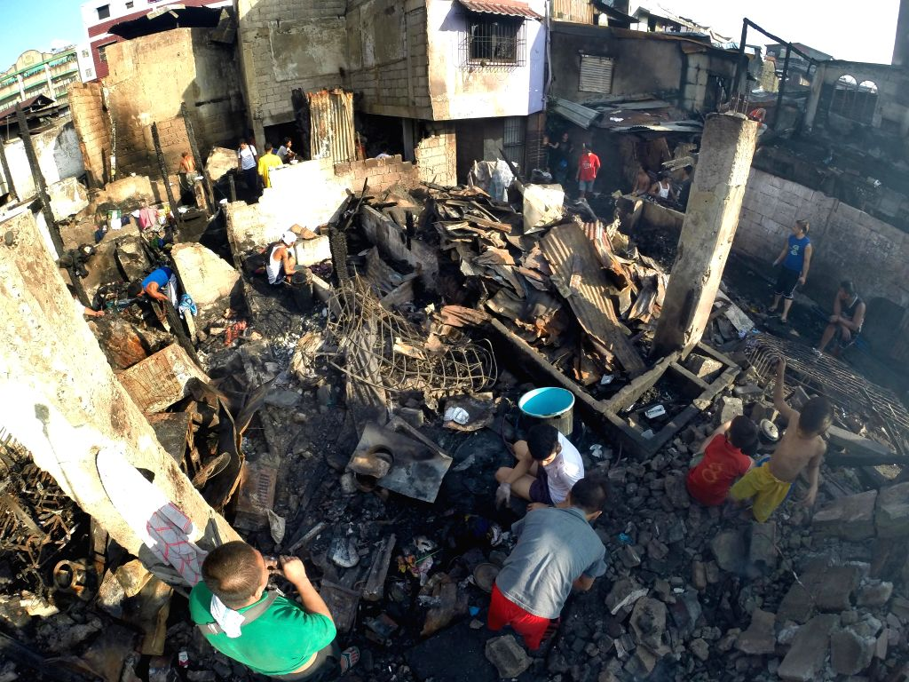 Residents look for reusable materials after a fire hit a slum area in Manila, the Philippines, Jan. 13, 2015. More than 100 houses were razed in the fire, leaving ...
