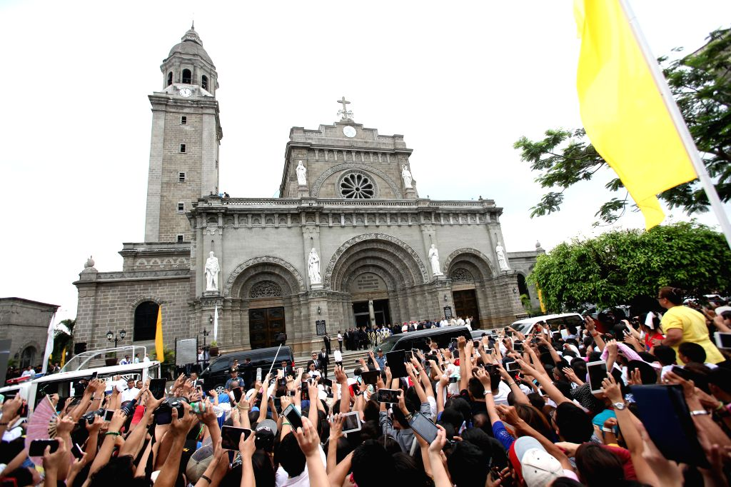 People take photos of Pope Francis at the Manila Cathedral in Manila, the Philippines, Jan. 16, 2015. Visiting Pope Francis challenged on Friday Philippine political