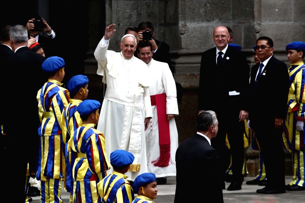Pope Francis (center L) waves to the crowd before entering the Manila Cathedral in Manila, the Philippines, Jan. 16, 2015. Visiting Pope Francis challenged on Friday