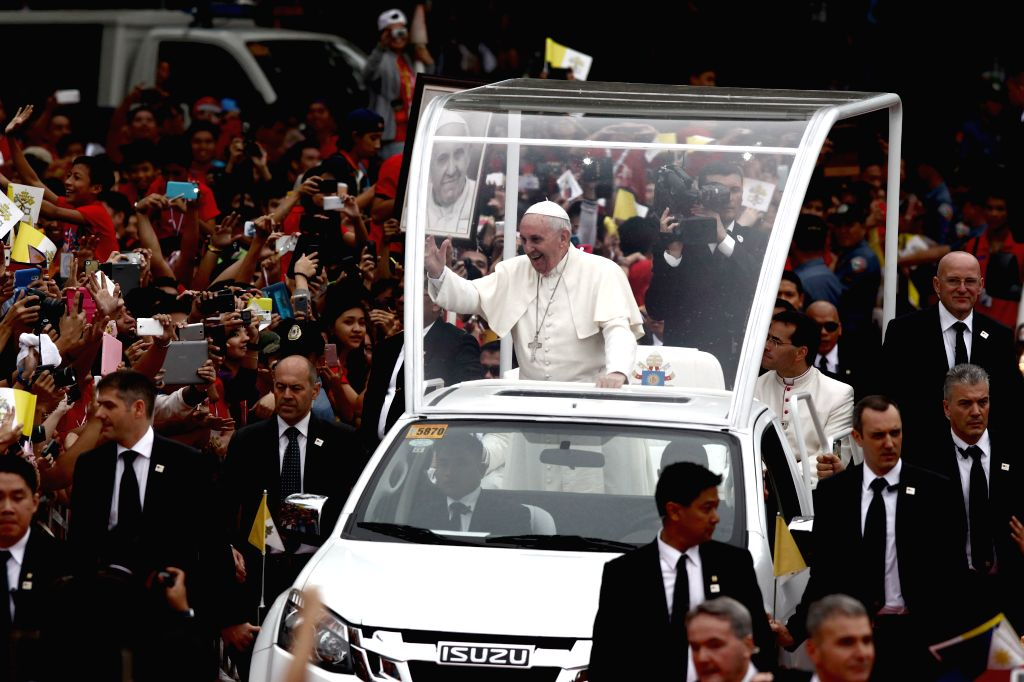 Pope Francis (C) waves to the crowd inside the campus of the University of Santo Tomas in Manila, the Philippines, Jan. 18, 2015. The leader of the Roman Catholic ..