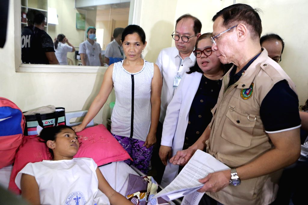 MANILA, July 16, 2019 - Philippine Health Secretary Francisco Duque (R) checks patients at a dengue ward of the San Lazaro Hospital in Manila, the Philippines, July 16, 2019. The Philippines declared ...