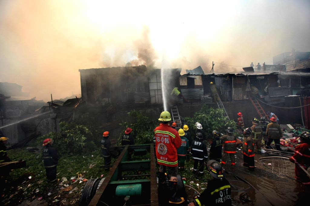 Firefighters try to put out a fire at a slum area in Manila, the Philippines, March 3, 2015. The fire razed 50 homes, hours after more than 5,000 shanties were razed ...