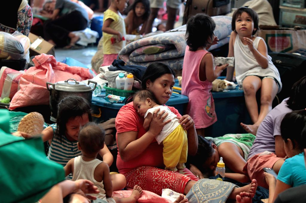 Residents take shelter inside a basketball court which turned into an evacuation center in Manila, the Philippines, March 3, 2015. More than 10,000 families were ...