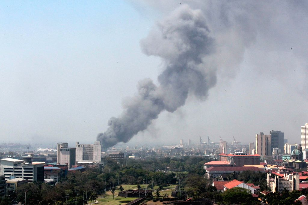 Smoke billows from a fire at a slum area in Manila, the Philippines, March 3, 2015. The fire razed 50 homes, hours after more than 5,000 shanties were razed in the ...