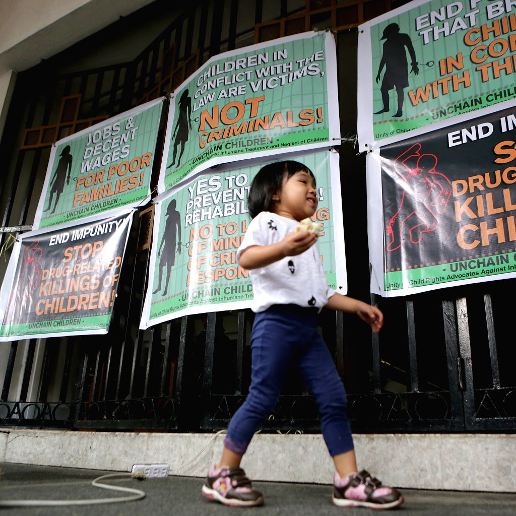 MANILA, March 4, 2017 - A girl walks past placards during an activity for the rights of children in Manila, the Philippines, March 4, 2017. The activity was organized to call for the end of poverty ...