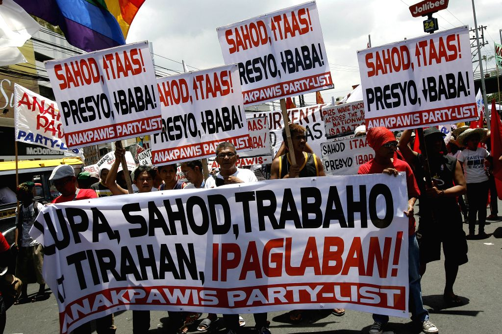 Activists hold placards calling for higher wage and lower price on basic commodities during the Labor Day protest rally in Manila, Philippines, May 1, 2014. ...