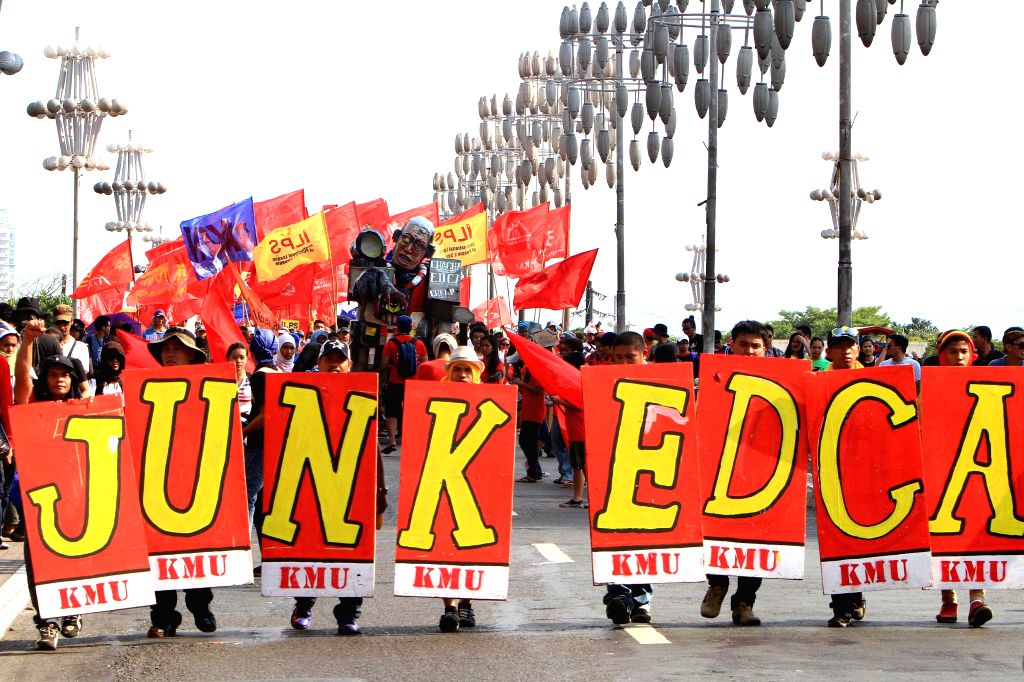 Activists hold placards calling for the junking of the Enhanced Defense Cooperation Agreement (EDCA) between the Philippines and the U.S. during the Labor Day protest .