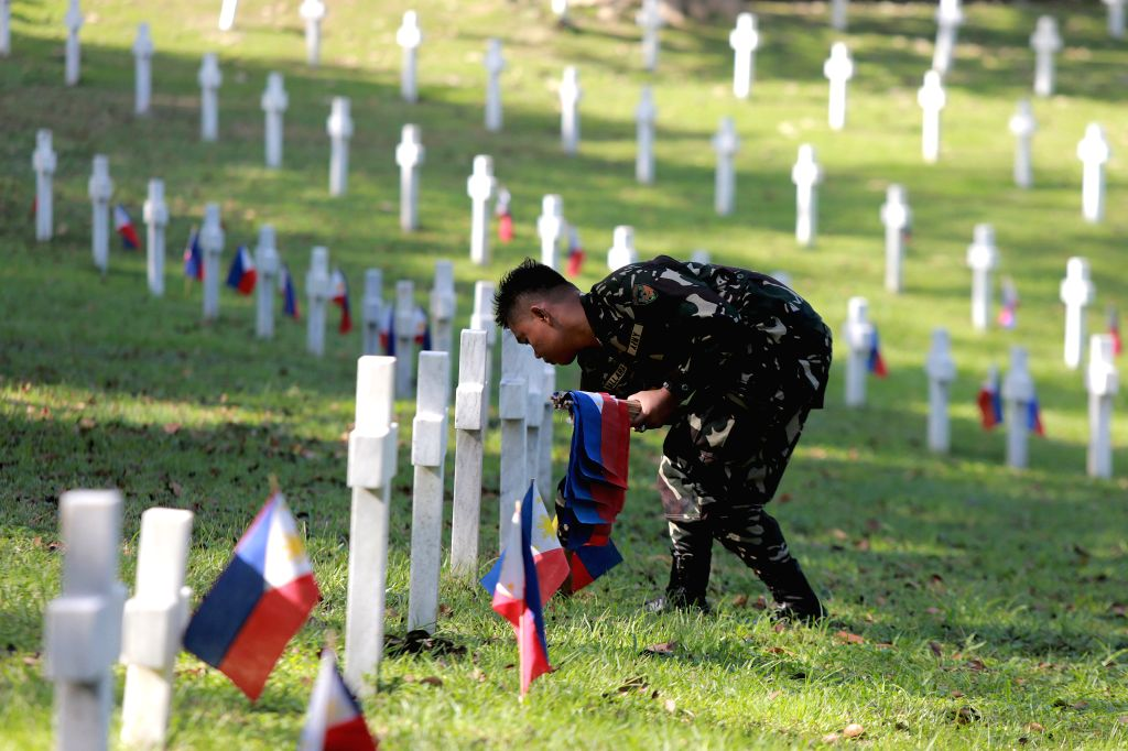 MANILA, Oct. 31, 2016 - A soldier places Philippine flags on tombs of World War II veterans at the Libingan ng mga Bayani in Taguig City, south of Manila, the Philippines, Oct. 31, 2016. Millions of ...