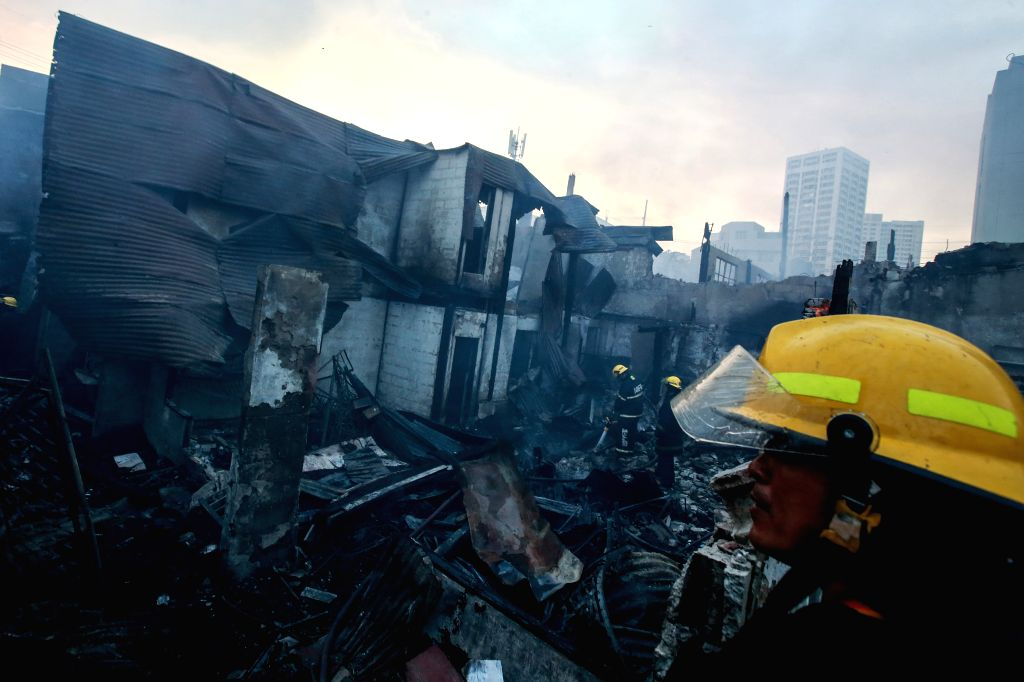 MANILA, Sept. 26, 2019 - Firefighters try to put out a fire at a residential area in Manila, the Philippines, Sept. 26, 2019. Around 1,000 individuals were affected by the fire, including 900 ...