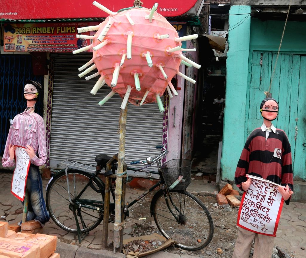 Mannequins and a dummy of coronavirus put up on display with messages for the public to spread awareness about the disease in Kolkata during the extended nationwide lockdown imposed to ...