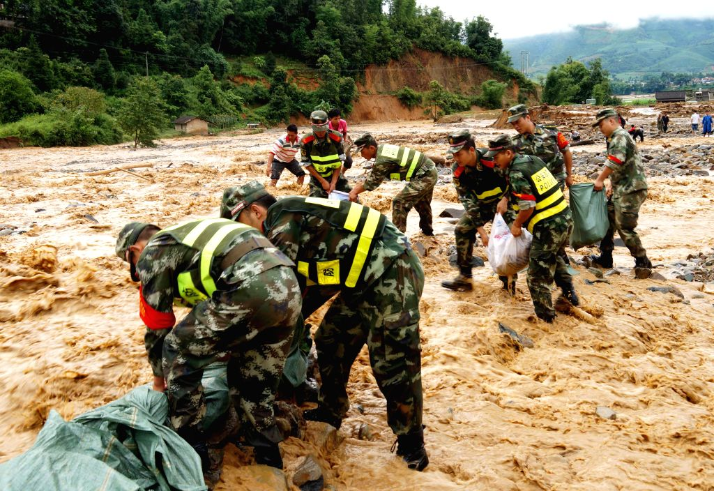 Rescuers set a temporary flood-control dam at Manghai Town in Dai-Jingpo Autonomous Prefecture of Dehong, southwest China's Yunnan Province, July 23, 2014. A ...