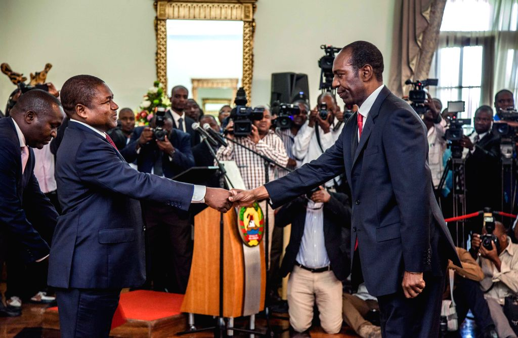 Mozambique's President Filipe Nyusi (L) shakes hands with Prime Minister Carlos Agostinho do Rosario during the swearing-in ceremony of the new cabinet in ... - Carlos Agostinho