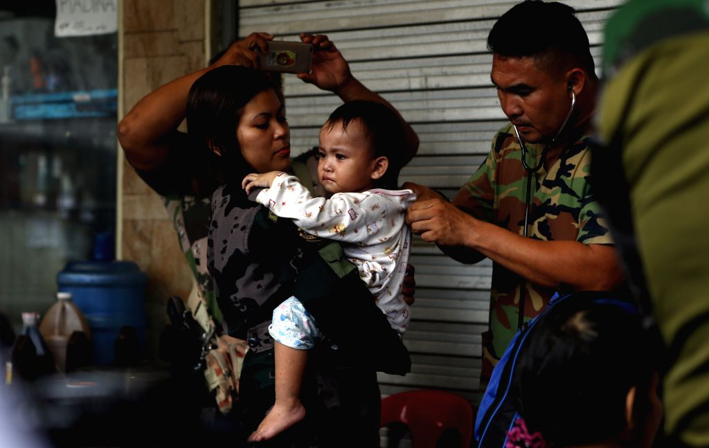 MARAWI, June 25, 2017 - A military doctor checks the health condition of a baby who was rescued from Marawi, Philippines, on June 25, 2017. Five civilians, who had been trapped in Marawi, were ...