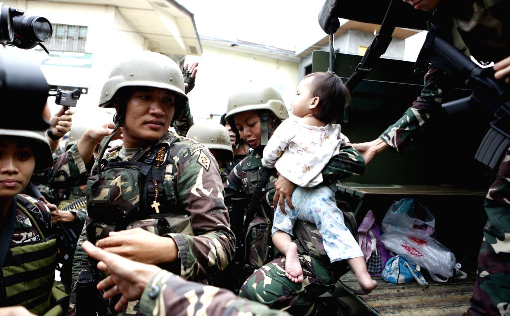 MARAWI, June 25, 2017 - A soldier carries a baby who was rescued from Marawi, Philippines, on June 25, 2017. Five civilians, who had been trapped in Marawi, were rescued by government negotiators ...
