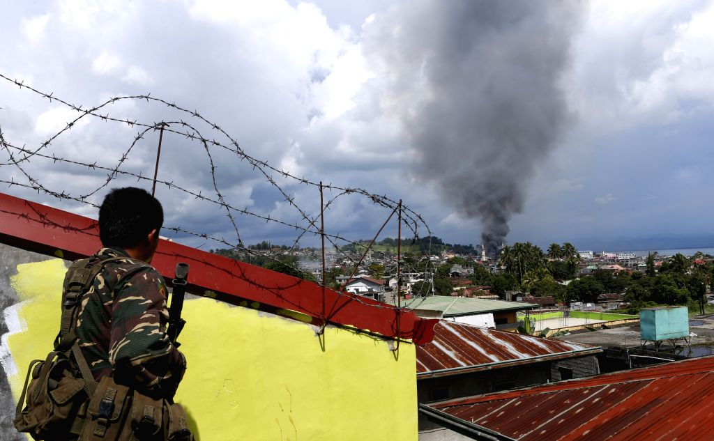 MARAWI, June 27, 2017 - A soldier watches a plume of black smoke billowing from downtown of Marawi City, the Philippines, on June 27, 2017. The Philippine government sticks to its policy of no ...