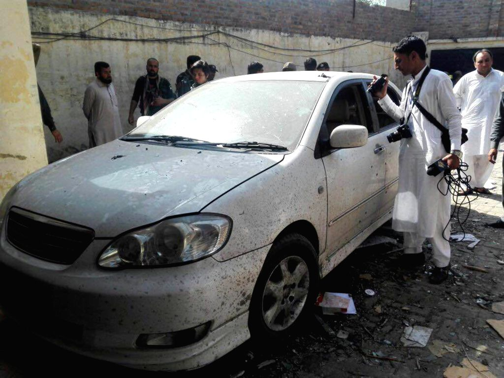 MARDAN, April 19, 2016 - People gather around a damaged vehicle at the suicide blast site in northwest Pakistan's Mardan, on April 19, 2016. At least 22 people were injured when a suicide blast hit a ...