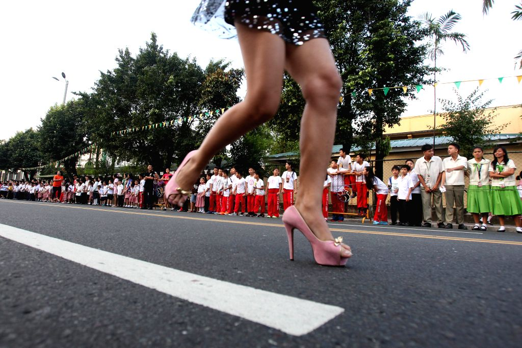"Marikina City: A woman wearing high heels runs during the ""Tour de Takong"" (Tour of High Heels) in Marikina City, the Philippines, on Nov. 13, 2014. Residents took part in the annual Tour .."