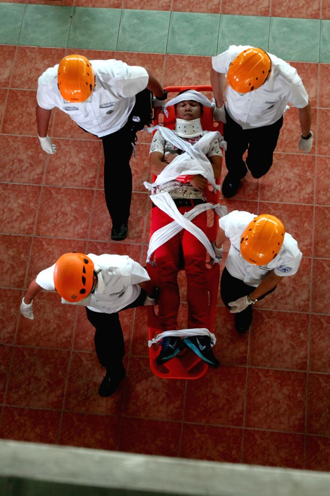 Rescuers carry a mock victim during the Nationwide Simultaneous Earthquake Drill in Marikina City, the Philippines, March 27, 2015. (Xinhua/Rouelle ...