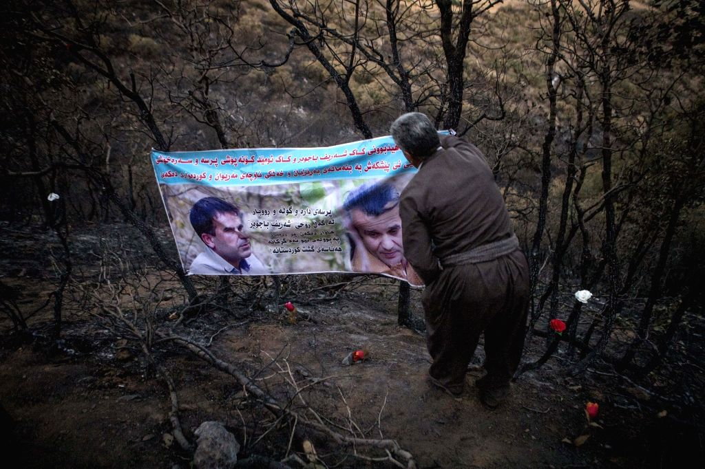 MARIVAN (IRAN), Sept. 4, 2018 A local man adjusts a poster of the victims of wildfire in a forest outside Marivan city, western Iran, on Sept. 3, 2018. Four people were killed in the ...
