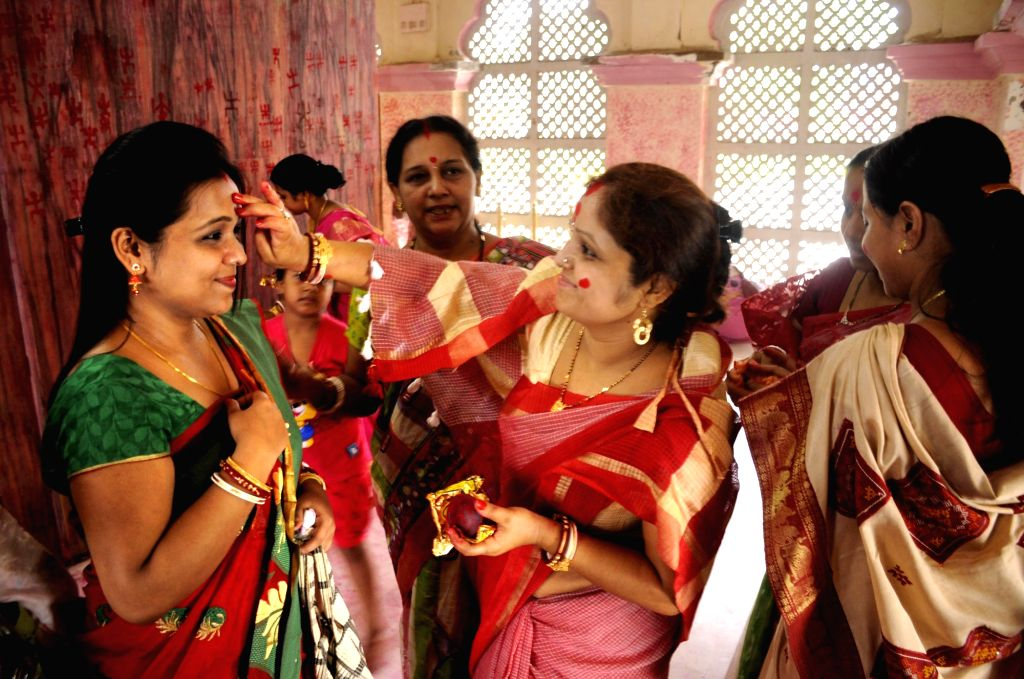 Married women apply vermilion on each others face during Ambubachi festival at Laxminarayana temple in Agartala on June 23, 2016. The week long Ambubachi festival that started yesterday is ...