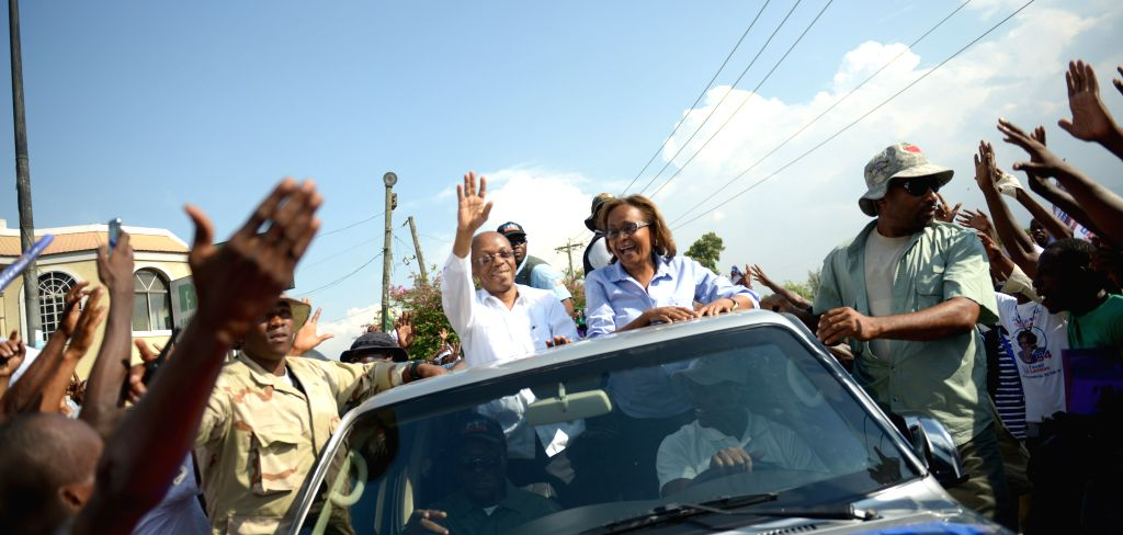 Maryse Narcisse (top R), presidential candidate of Fanmi Lavalas party, along with former Haitian President Jean-Bertrand Aristide (top L) attends a campaign ...