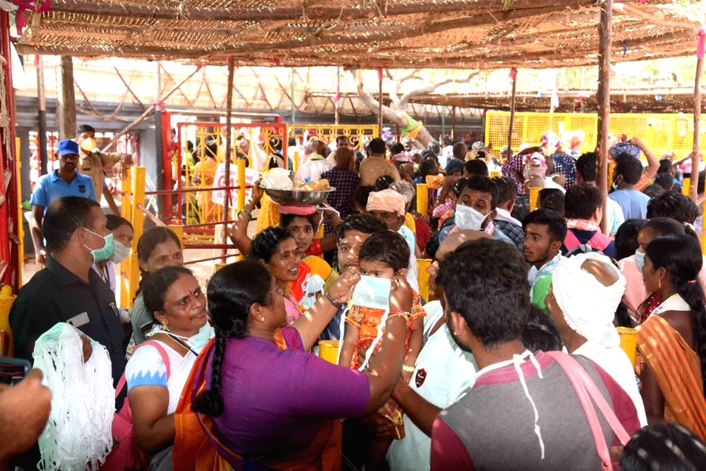 Masks being distributed among the devotees as a precautionary measure against coronavirus during Asia's biggest tribal fair, Sammakka-Saralamma jatara at Medaram in Telangana's Mulugu ...
