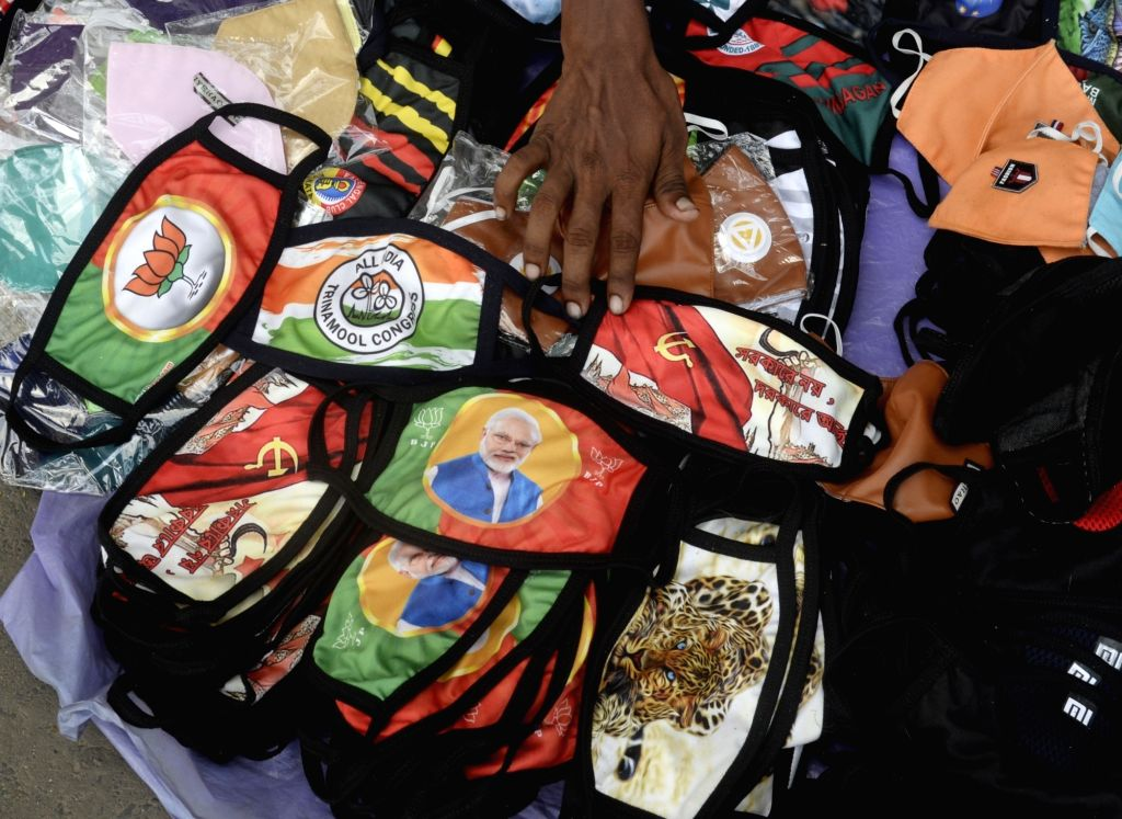 Masks with the pictures of Prime Minister Narendra Modi and symbols of various political parties printed on them being sold at a streetside amid COVID-19 pandemic, in Kolkata on July 2, 2020. - Narendra Modi