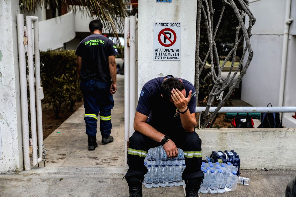 MATI (GREECE), July 24, 2018 A firefighter takes a break in Mati, a seaside town east of Athens, Greece, on July 24, 2018. The number of killed in the devastating fires near Athens was ...