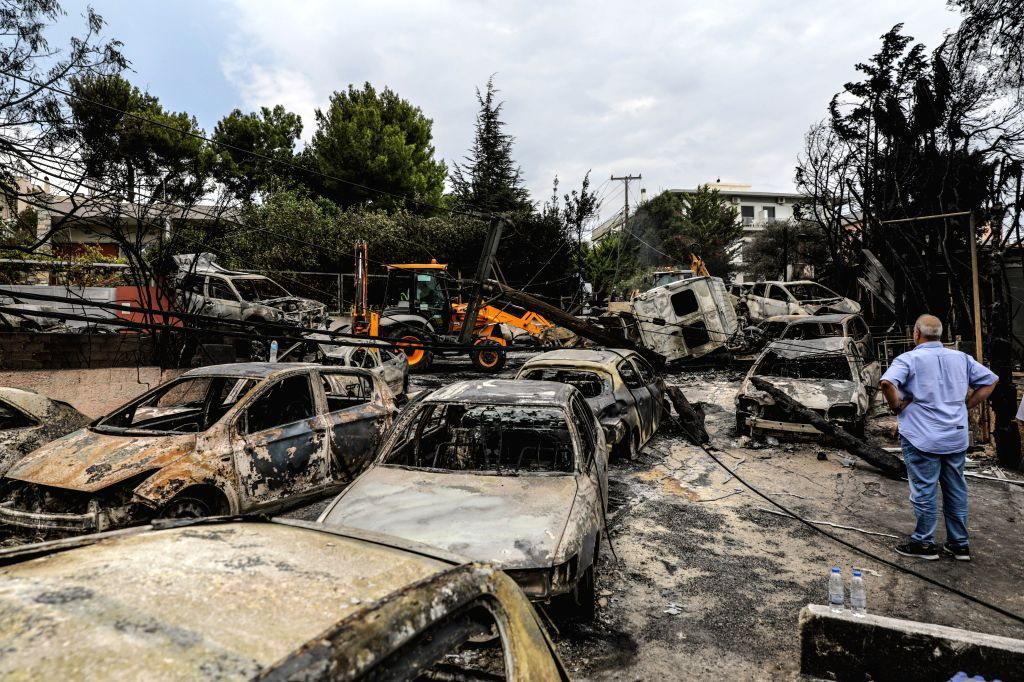 MATI (GREECE), July 24, 2018 A man looks at burned vehicles in Mati, a seaside town east of Athens, Greece, on July 24, 2018. The number of killed in the devastating fires near Athens was ...