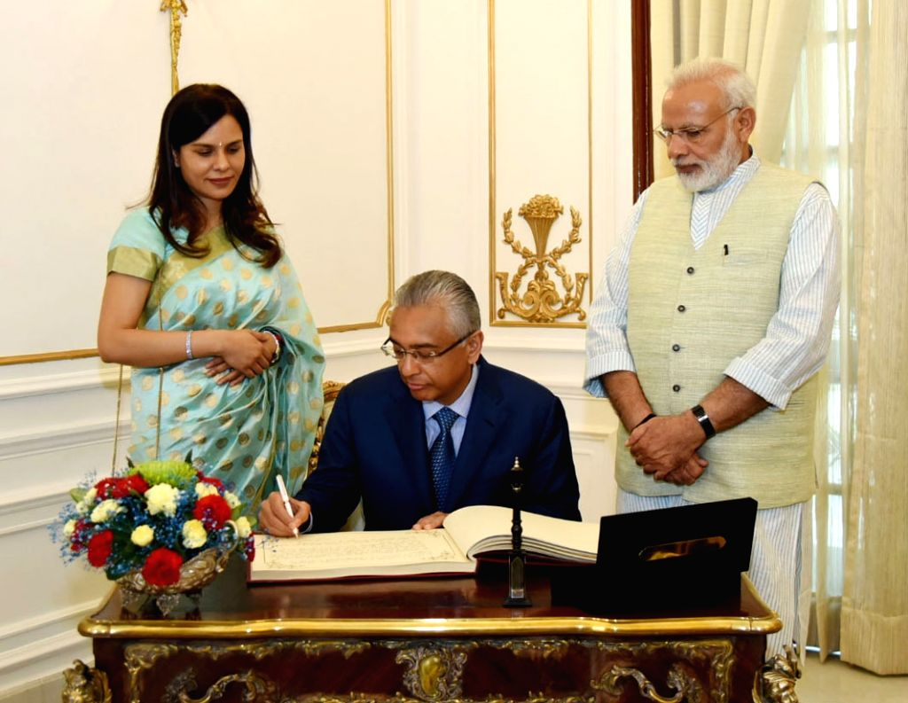 Mauritian Prime Minister Pravind Kumar Jugnauth signs the visitors' book, at Hyderabad House, in New Delhi on May 27, 2017. Also seen Prime Minister Narendra Modi. - Pravind Kumar Jugnauth and Narendra Modi