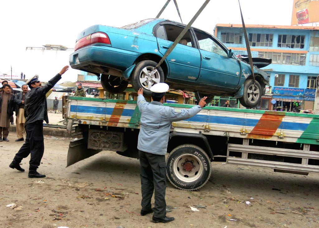 Mazar (Afghanistan): Afghan policemen transfer a damaged vehicle following a blast in Mazar province in northern Afghanistan, Nov. 28, 2014. Three civilians were injured as a bomb blast rocked a ...